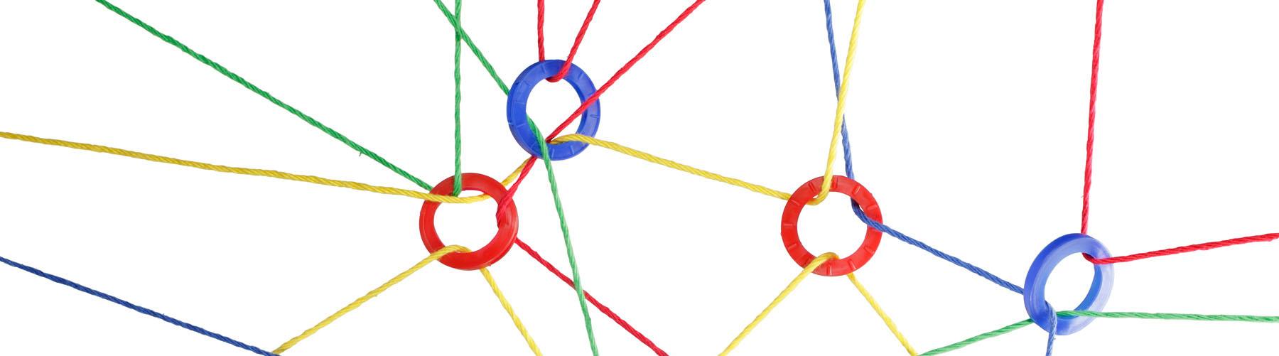 Ringe, die über bunte Fäden miteinander vernetzt sind